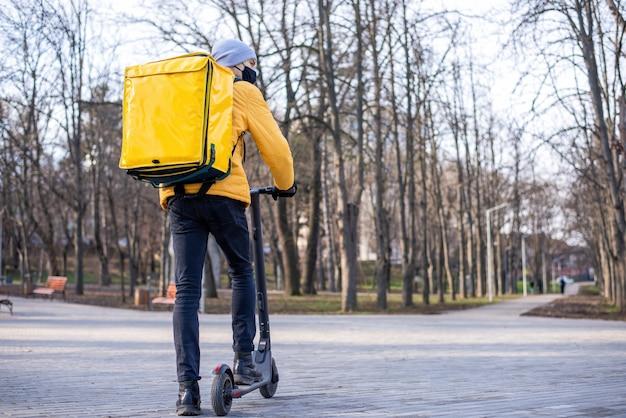 Mężczyzna dostawy żywności na skuterze w parku. czarna maska medyczna, żółty plecak i kurtka. zimowy
