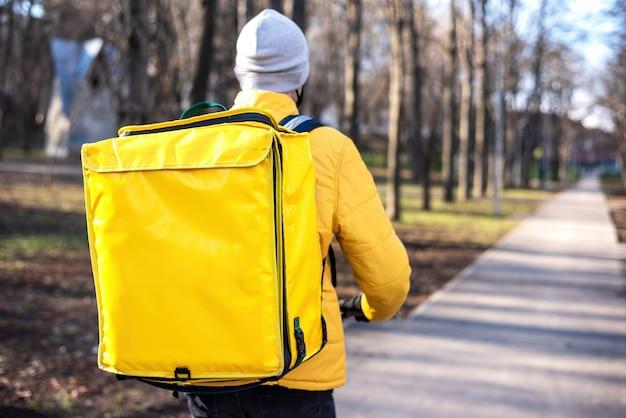 Mężczyzna dostawy żywności na skuterze w parku. żółty plecak i kurtka. zimowy