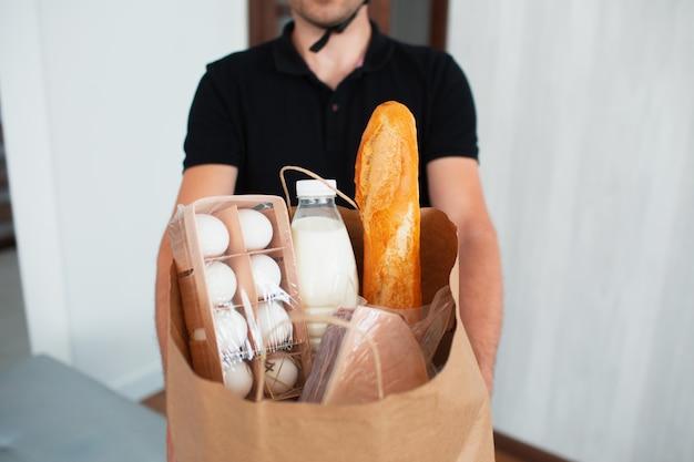 Mężczyzna dostawy żywności przyniósł jedzenie do domu młodej kobiety. chce zapłacić za zamówienie za pomocą aplikacji w smartfonie.