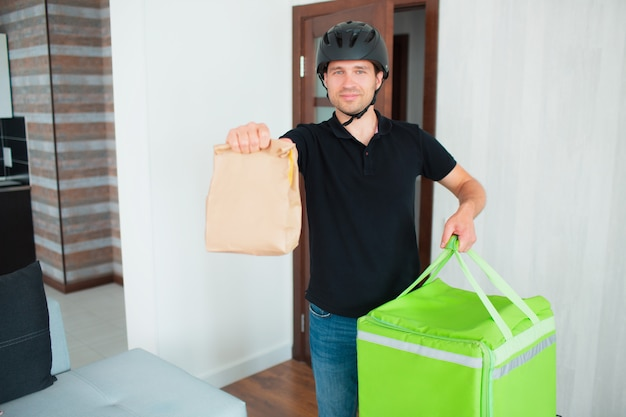 Mężczyzna dostawy żywności przyniósł jedzenie do domu młodej kobiety.