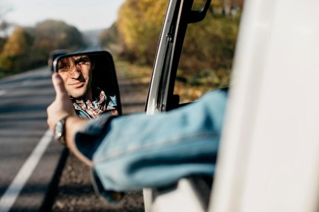 Mężczyzna dostosowując swoje lustro w samochodzie