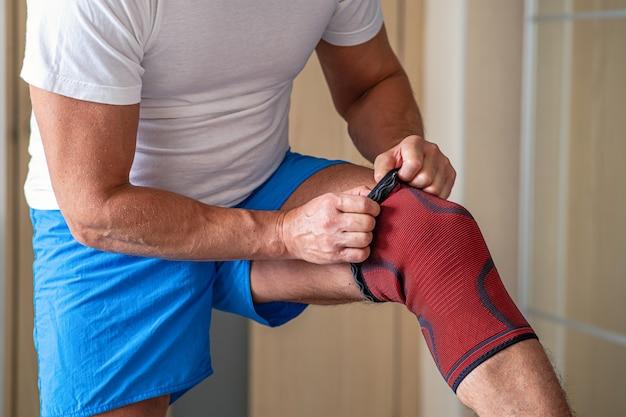 Mężczyzna dostosowuje bandaż uciskowy na stawie kolanowym. kontuzja sportowa.