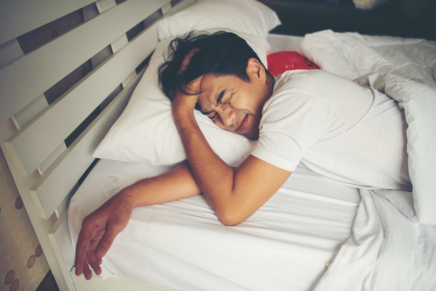 Mężczyzna dosypianie na łóżku w ranku