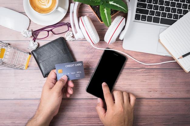 Mężczyzna dotyka czarnego ekranu telefonu komórkowego i trzyma kartę kredytową na portfelu