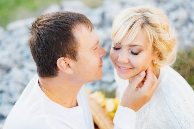 Mężczyzna dotyka dłonią policzka kobiety z zamkniętymi oczami, siedząc na kocu