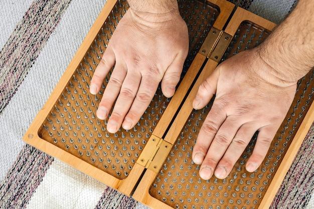Mężczyzna dotyka drewnianej deski sadhu do jogi ostrymi paznokciami