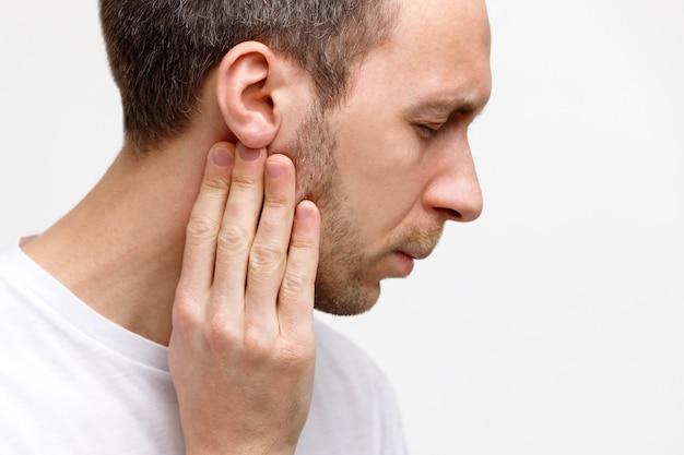 Mężczyzna dotyka gruczołów chłonnych palcami w pobliżu ucha