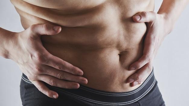 Mężczyzna dotyka jego zbliżenie tłuszczu brzuch, otyłość, utrata masy ciała mężczyzn i koncepcja diety