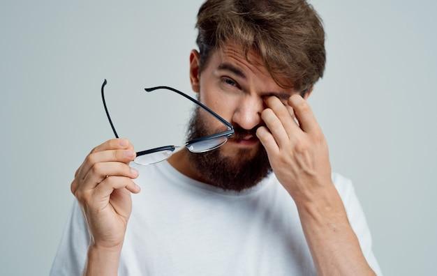 Mężczyzna dotyka oczu rękami i okularami problemy ze wzrokiem na szarym tle