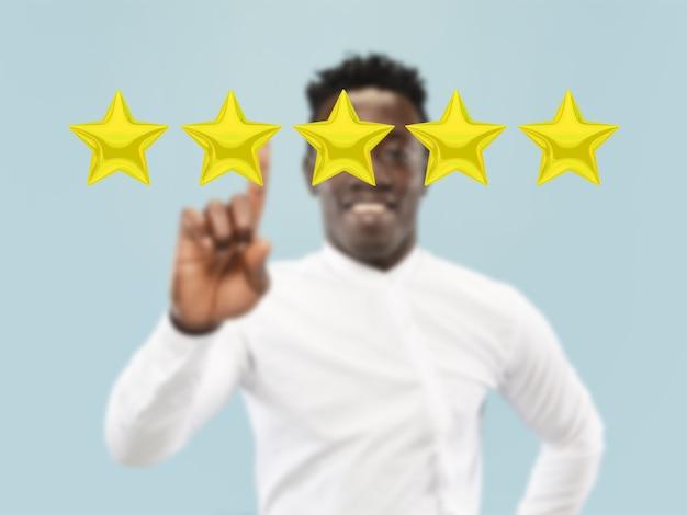 Mężczyzna dotyka pięciogwiazdkowego symbolu, aby zwiększyć ocenę firmy, aplikacji lub usługi. pozostawia swoją stawkę za produkt, specjalistę, program. koncepcja biznesu, technologii, marketingu, reklamy, sprzedaży, komunikacji.