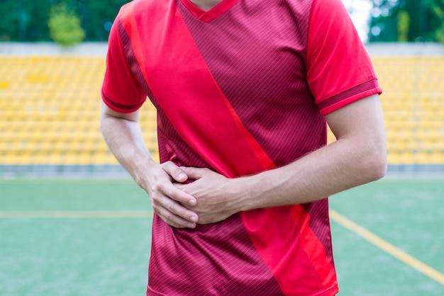 Mężczyzna dotyka prawej strony na tle stadionu