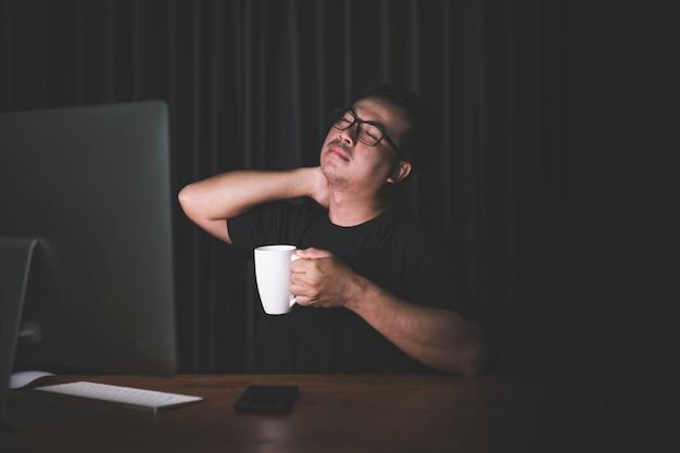 Mężczyzna dotyka szyi z powodu bólu spowodowanego pracą przy komputerze