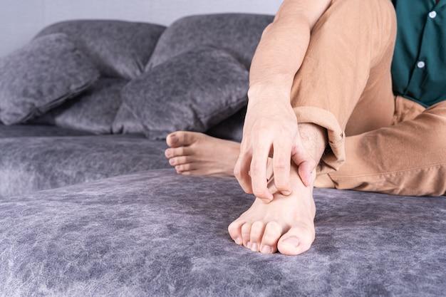 Mężczyzna drapie się w stopę siedząc na kanapie