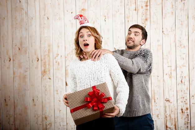 Mężczyzna dusi dziewczyny mienia bożych narodzeń prezent nad drewnianą ścianą