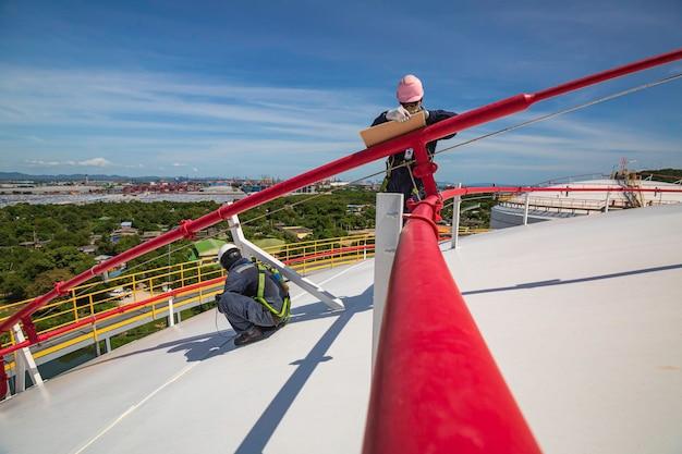 Mężczyzna dwóch pracowników służy do kontroli grubości ultradźwiękowej płyty dachowej kopuły górnej części zbiornika magazynowego.