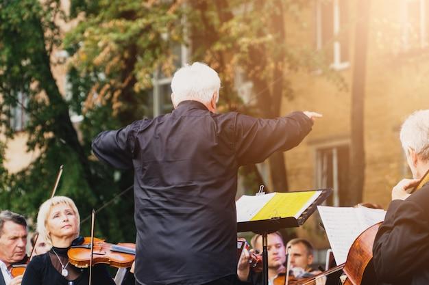 Mężczyzna dyrygent ze swoim zespołem na festiwalu wyprzedza w słonecznej ukraińskiej połtawie