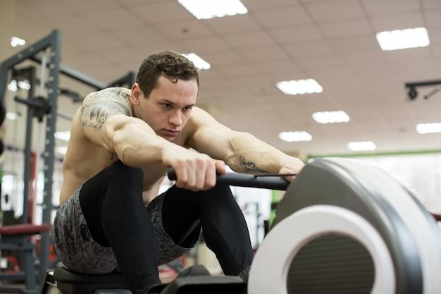 Mężczyzna działający wioślarski ćwiczenie w gym