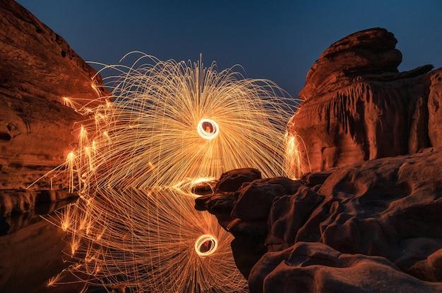 Mężczyzna dzierżący okrągłą płonącą iskrę z wełny stalowej w bystrzach skalnych wielkiego kanionu odbicie nad rzeką w hat chom dao