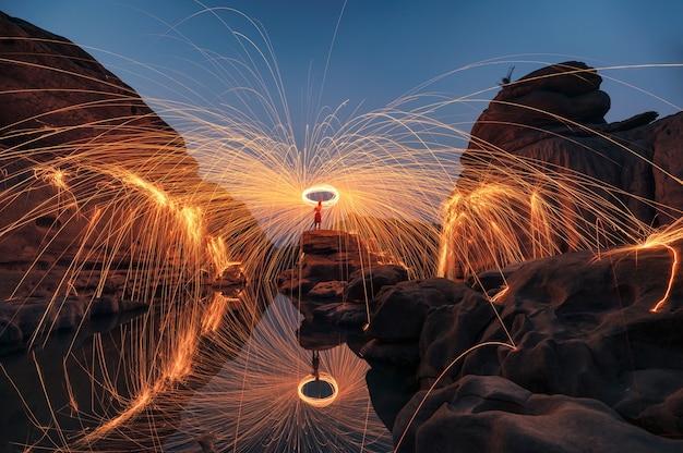 Mężczyzna dzierżący okrągłą płonącą iskrę z wełny stalowej w skalnych progach wielkiego kanionu odbicie nad rzeką w hat chom dao, ubon ratchathani