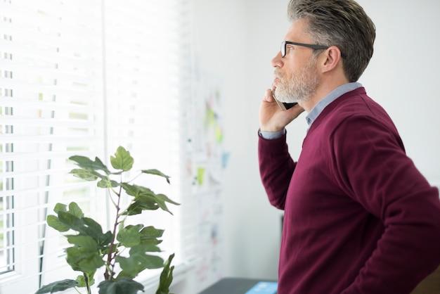 Mężczyzna dzwoni do klienta obok okna