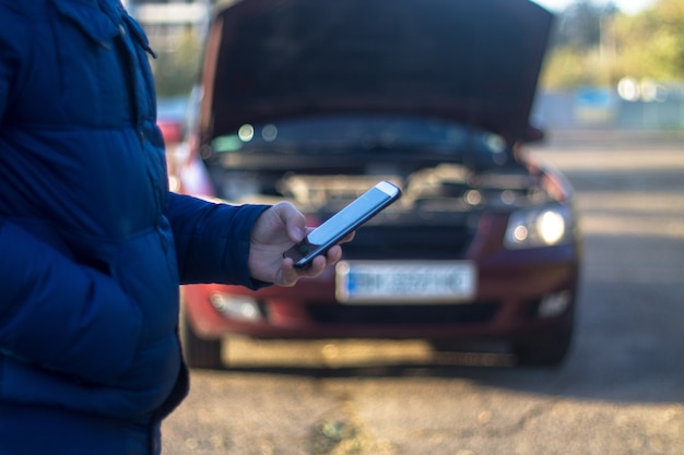 Mężczyzna dzwoni do serwisu samochodowego z powodu kłopotów ze swoim zepsutym samochodem w tle widać zamazany samochód
