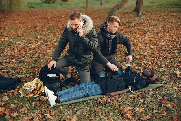 Mężczyzna dzwoni po karetkę. afrykańska dziewczyna leży nieprzytomna. udzielanie pierwszej pomocy w parku