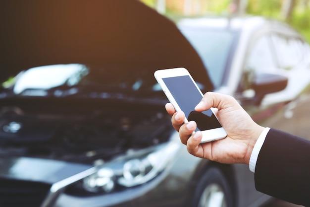 Mężczyzna dzwoni przez telefon komórkowy do mechanika samochodowego, ponieważ samochód się zepsuł