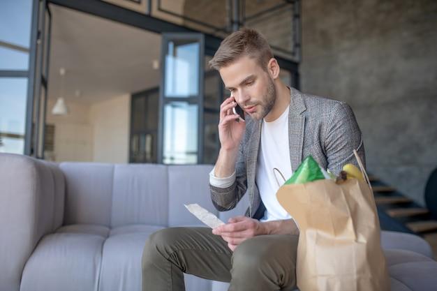Mężczyzna dzwoniący, aby złożyć wniosek o zwrot kosztów w supermarkecie