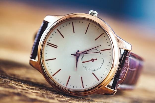 Mężczyzna elegancki zegarek na drewnianym stołowym tle