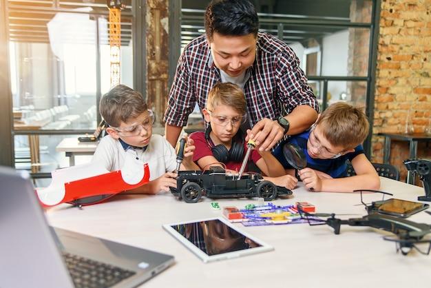 Mężczyzna elektronik z europejskimi dziećmi w wieku szkolnym pracujący w inteligentnym szkolnym laboratorium i testujący model samochodu elektrycznego sterowanego radiowo.
