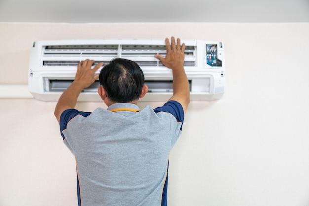 Mężczyzna elektryk instaluje klimatyzację w domu klienta
