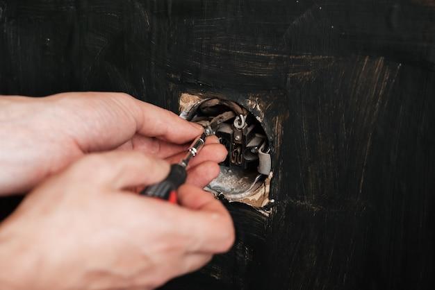 Mężczyzna elektryk naprawia stary wadliwy gniazdko elektryczne za pomocą śrubokręta