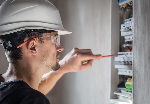 Mężczyzna, elektryk pracujący w tablicy rozdzielczej z bezpiecznikami. instalacja i podłączenie sprzętu elektrycznego. ścieśniać.