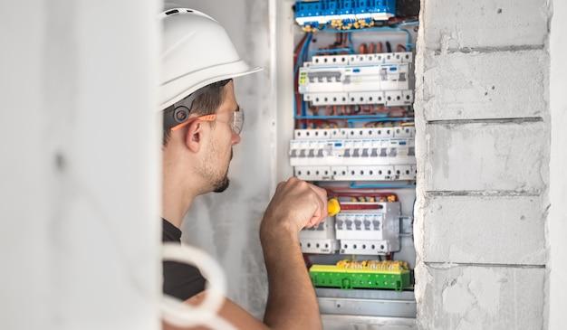 Mężczyzna, elektryk pracujący w tablicy rozdzielczej z bezpiecznikami. instalacja i podłączenie sprzętu elektrycznego.