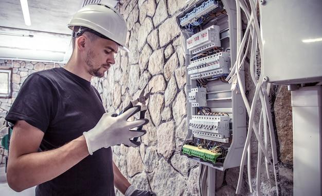 Mężczyzna elektryk pracuje w tablicy rozdzielczej za pomocą elektrycznego kabla łączącego