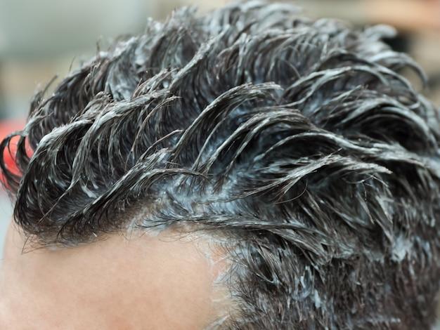 Mężczyzna farbuje włosy w salonie piękności. farbowanie męskich włosów