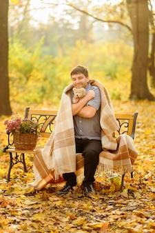 Mężczyzna figlarnie przytula małego misia. aby się ogrzać, mężczyzna schronił się w kocu. on siedzi na ławce w jesiennym parku.