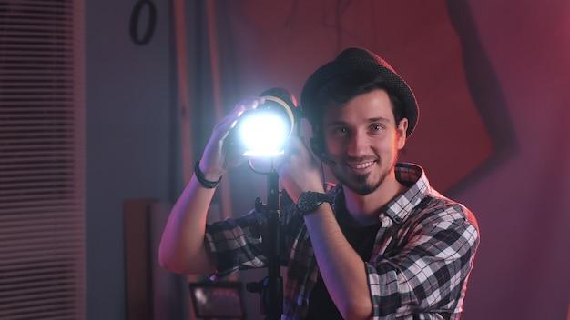 Mężczyzna filmowiec dostosowujący profesjonalny statyw oświetleniowy w studio, z włączonym oświetleniem