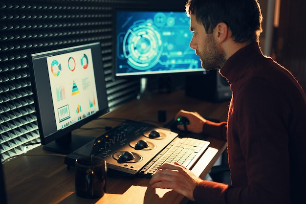 Mężczyzna filmowiec edytuje i wycina materiał i dźwięk na swoim komputerze osobistym