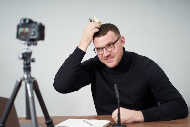 Mężczyzna filmujący bloga wideo na aparacie ze statywem dla obserwujących online. w mediach społecznościowych, influencer, nowej technologii i koncepcji internetu