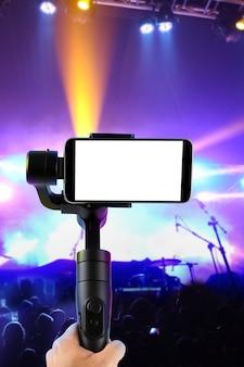 Mężczyzna filmujący smartfonem z pustym ekranem za pomocą stabilizatora gimbala, na białym tle na pokaz muzyczny. selektywna ostrość.
