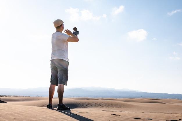 Mężczyzna filmuje się telefonem komórkowym na pustynnych wydmach. podróżujący twórca treści dla mężczyzn