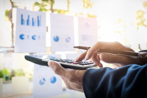 Mężczyzna finansów biznesowych oblicza numery budżetowe, faktury i doradca finansowy pracuje.