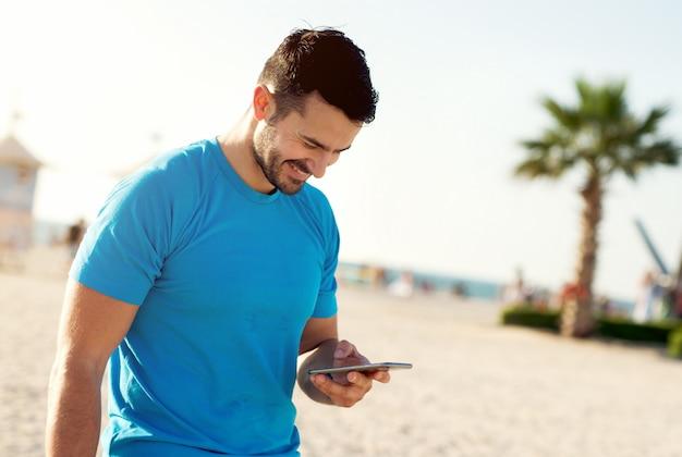 Mężczyzna fitness biegacz w słoneczny dzień sprawdzania swojego telefonu komórkowego ..