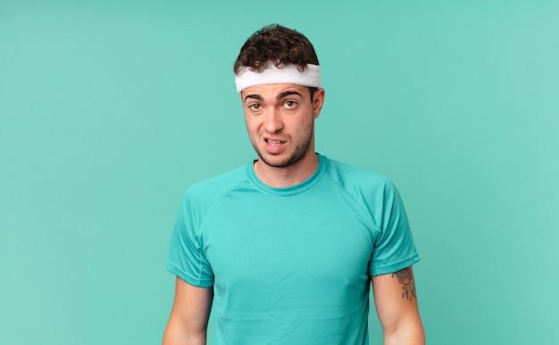 Mężczyzna fitness czuje się zdezorientowany i zdezorientowany, z tępym, oszołomionym wyrazem twarzy, patrzącym na coś nieoczekiwanego
