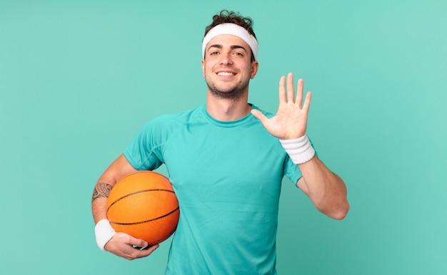 Mężczyzna fitness uśmiechający się i wyglądający przyjaźnie, pokazujący numer pięć lub piąty z ręką do przodu, odliczający w dół