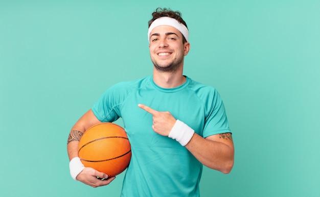Mężczyzna fitness uśmiechający się radośnie, czujący się szczęśliwy i wskazujący na bok i do góry, pokazujący obiekt w przestrzeni kopii