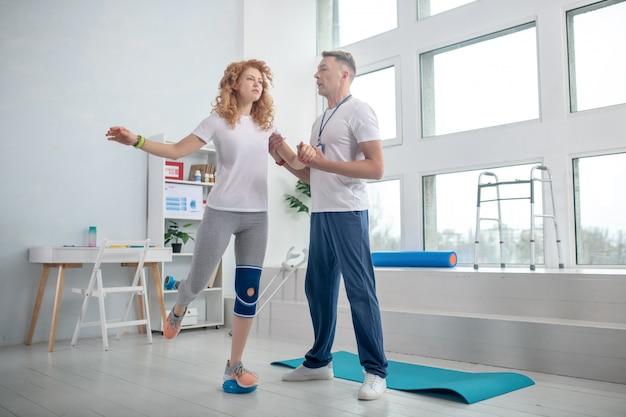 Mężczyzna fizjoterapeuty pomaga pacjentce zachować równowagę