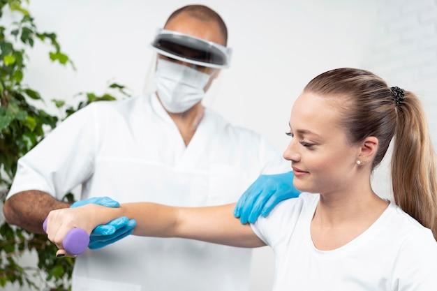 Mężczyzna fizjoterapeuty z osłoną twarzy sprawdzanie ramienia kobiety
