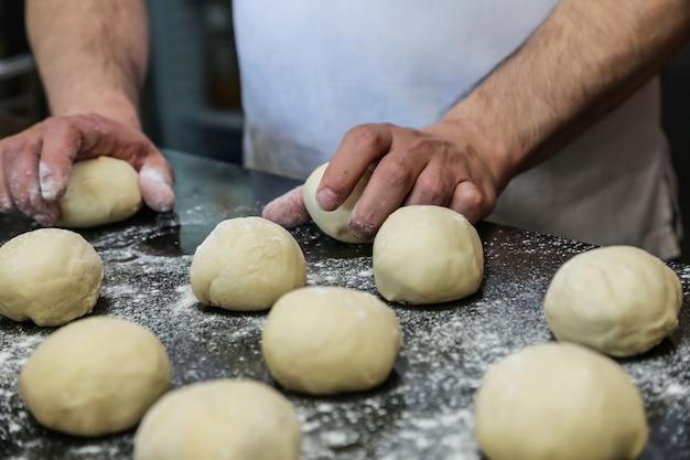Mężczyzna formuje torebki ciasta, patrząc z boku na dwa ramiona mąki